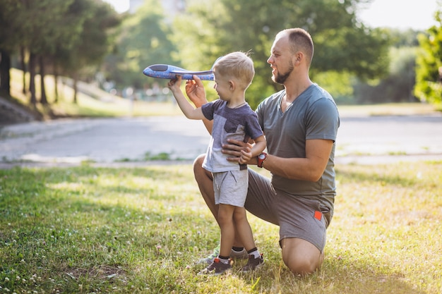 Pai com filho brincando com o avião de brinquedo no parque