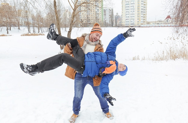 Pai com filho brincando no parque de inverno