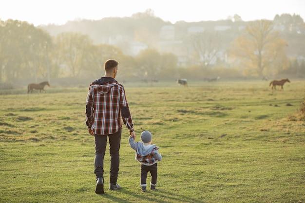Pai com filho caminhando em um campo de manhã