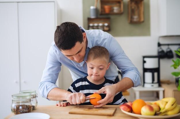Pai com filho de síndrome de down feliz dentro de casa na cozinha, preparando comida.