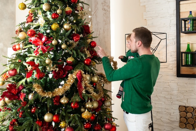 Pai com filho decorando árvore de natal
