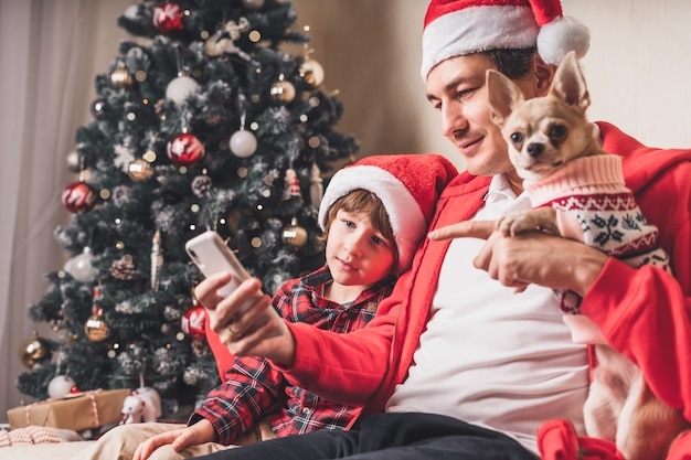 Pai com filho e cachorrinho com chapéu de papai noel segurando um celular