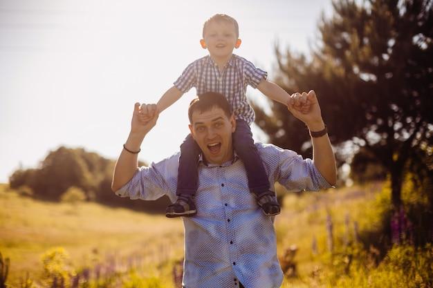 Pai com filho em seus ombros