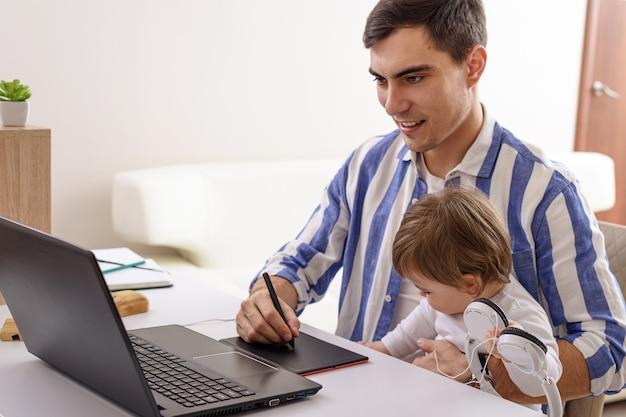 Pai com filho no colo, trabalho remoto em casa no laptop
