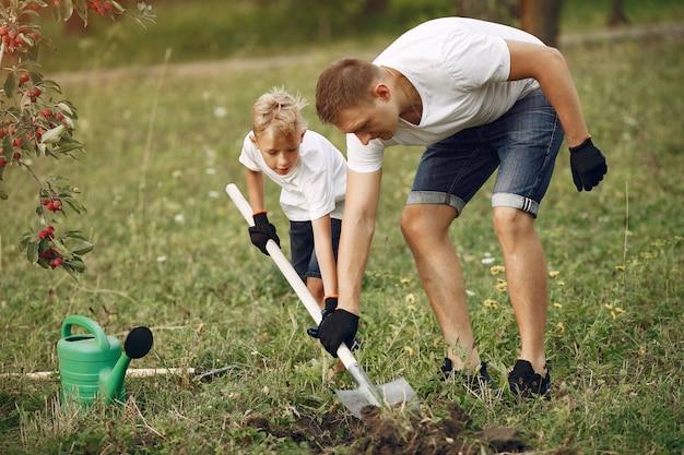 Pai com filho pequeno estão plantando uma árvore em um quintal