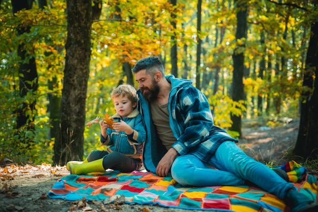 Pai com filho pequeno no parque outono. pai e filho em suéteres no parque. família feliz, pai e filho brincando e rindo na caminhada de outono.