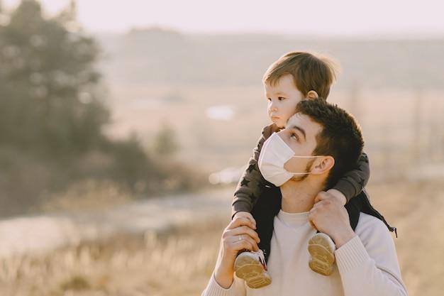 Pai com filho pequeno usando máscaras