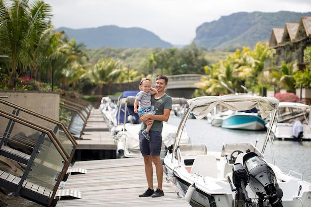 Pai com filho sentado no cais do mar. feliz pai e filho estão caminhando, olhando para os barcos.