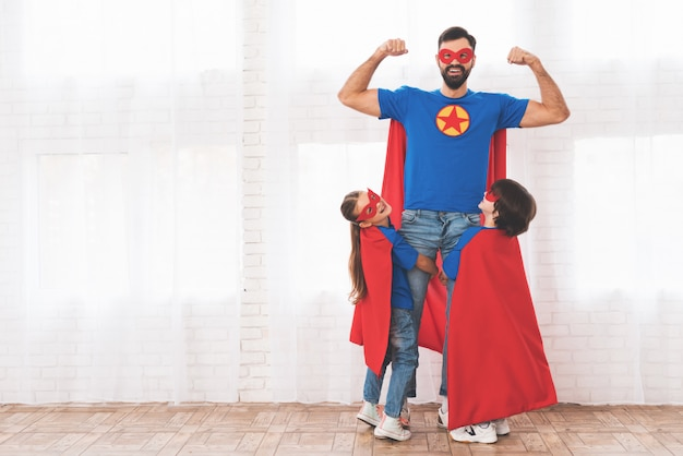 Pai com filhos em ternos vermelhos e azuis de super-heróis.