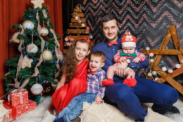 Pai com filhos em uma sessão de fotos de natal