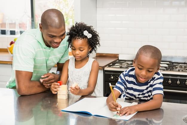 Pai com filhos na cozinha em casa