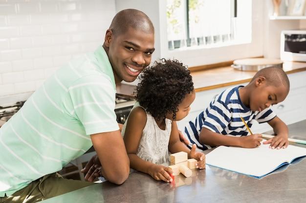 Pai com filhos na cozinha