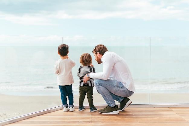 Pai, com, filhos, olhando mar