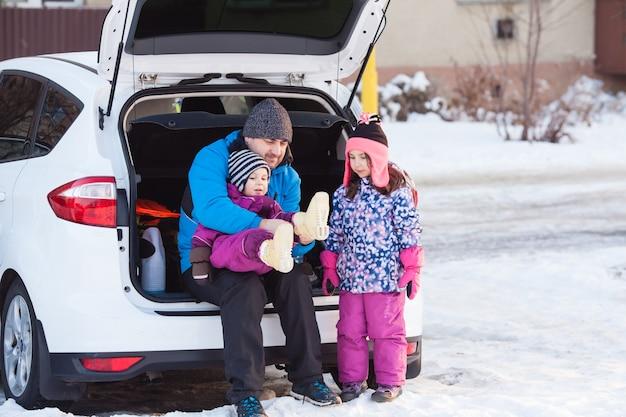 Pai com filhos sentado no porta-malas do carro se preparando para esquiar