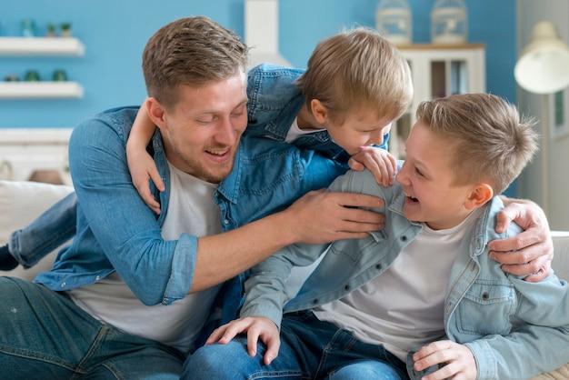 Pai com irmãos brincando dentro de casa