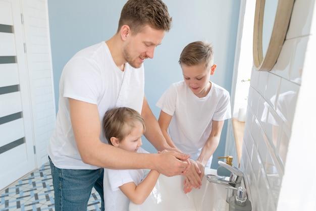 Pai com irmãos lavando as mãos vista alta