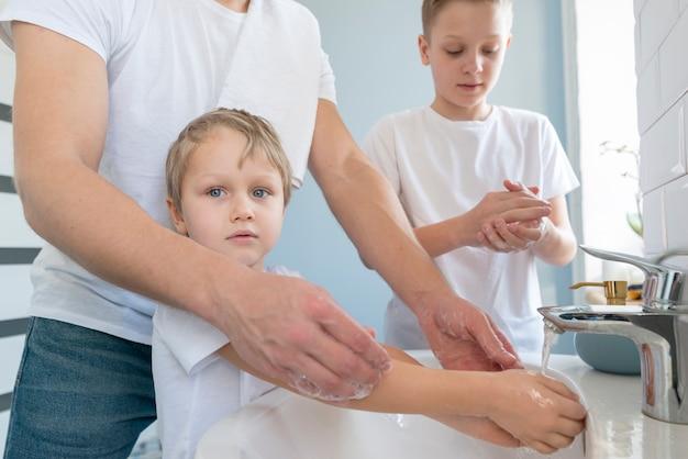 Pai com irmãos lavando as mãos vista lateral