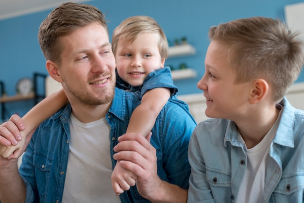 Pai com irmãos olhando um ao outro