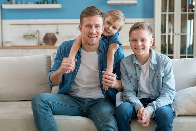Pai com irmãos sentados no sofá