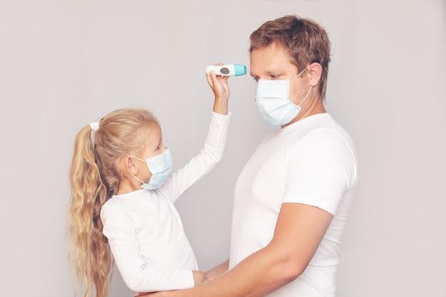 Pai com máscara médica mede a temperatura da filha com um termômetro eletrônico em um fundo isolado