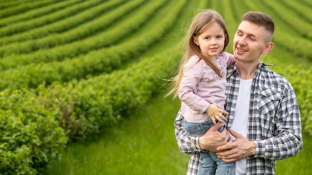 Pai com menina em terras agrícolas