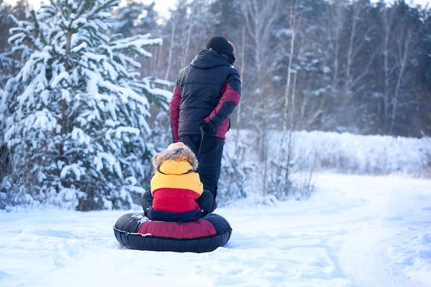 Pai com roupas de inverno puxando trenós com seu filho na floresta de inverno nevado. família feliz caminhada no bosque nevado, ao ar livre. vista traseira