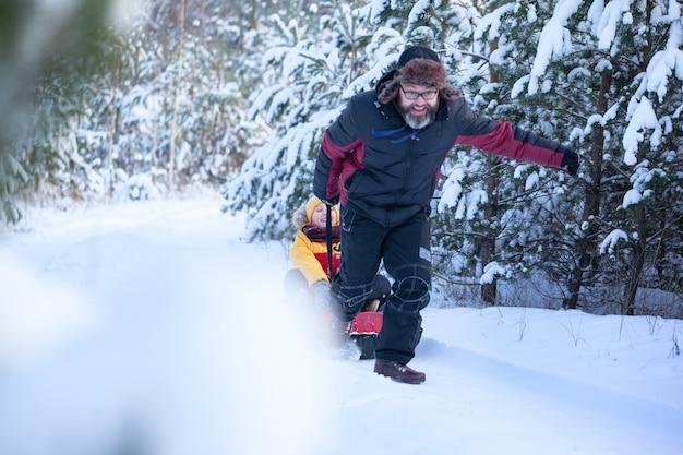 Pai com roupas de inverno puxando trenós com seu filho na floresta de inverno nevado. família feliz caminhada no bosque nevado, ao ar livre.