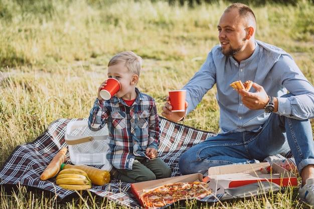 Pai com seu filho fazendo piquenique no parque