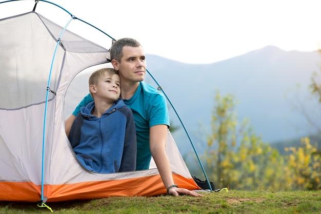 Pai com seu filho filho descansando juntos em uma tenda nas montanhas de verão.