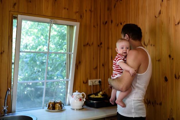Pai com um bebê pequeno nos braços está preparando o jantar. interior de uma casa de campo