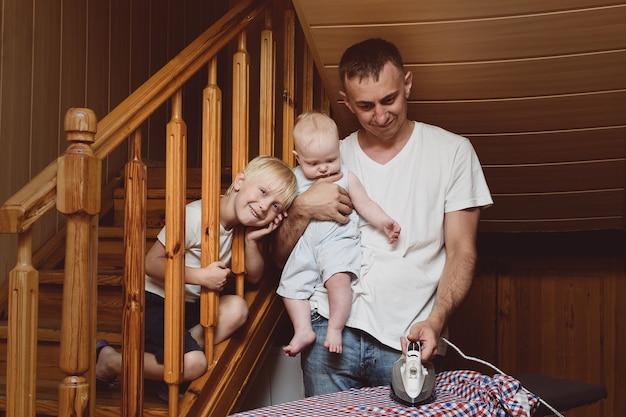 Pai com uma criança pequena nos braços passando roupa de cama