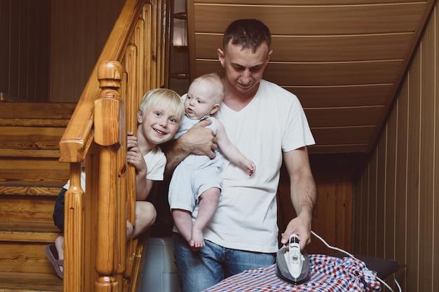 Pai com uma criança pequena nos braços passando roupa