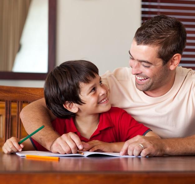 Pai confiante ajudando seu filho a fazer a lição de casa