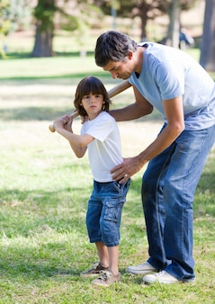 Pai confiante que ensina béisbol a seu filho