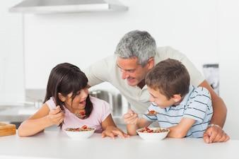 Pai conversando com seus filhos durante o café da manhã