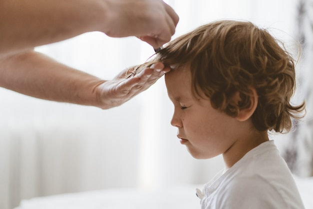 Pai corta o cabelo do filho na sala. família durante quarentena