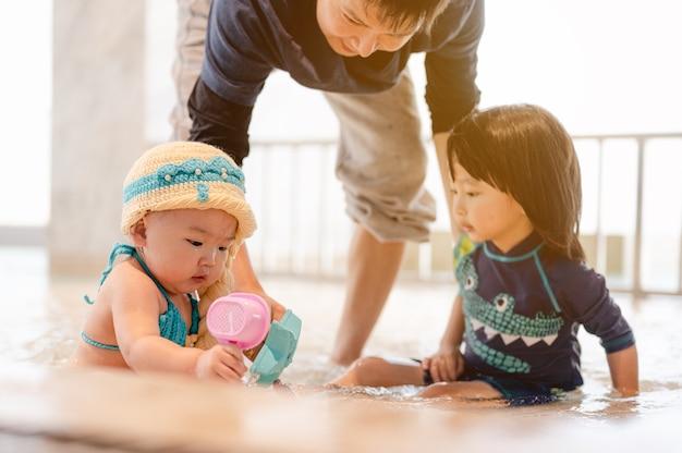 Pai cuida de seu filho e filha brincando com brinquedos na piscina do hotel se divertindo