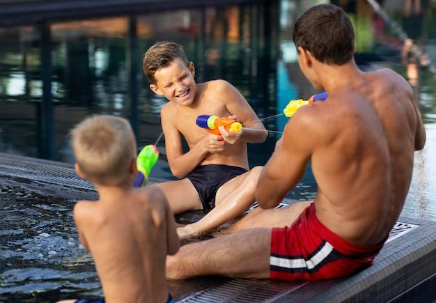 Pai curtindo um dia com seus filhos na piscina