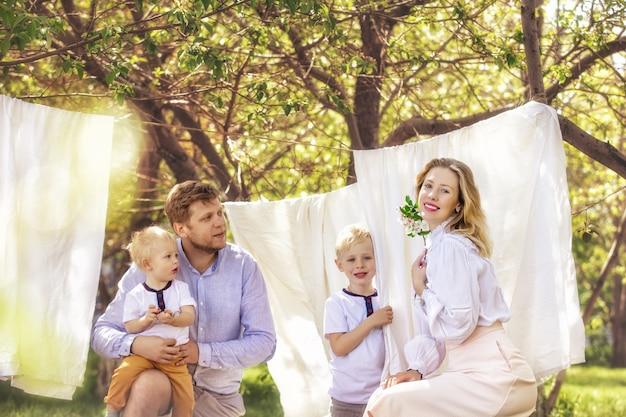 Pai da família, mãe e dois filhos lindos e felizes juntos penduram roupas limpas no jardim