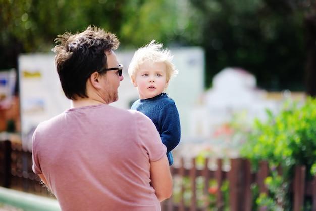 Pai da idade média com seu filho pequeno que anda ao ar livre.
