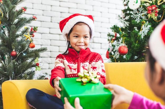 Pai dando caixa de presente de natal para menina bonita criança asiática na celebração de natal