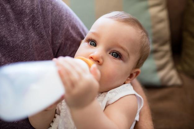 Pai dando leite para a menina em casa