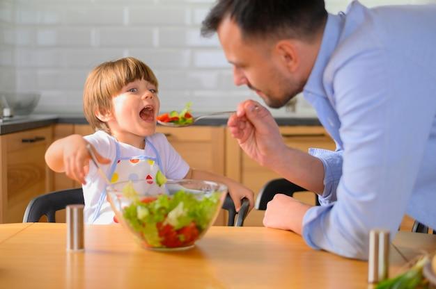 Pai dando salada ao filho para comer