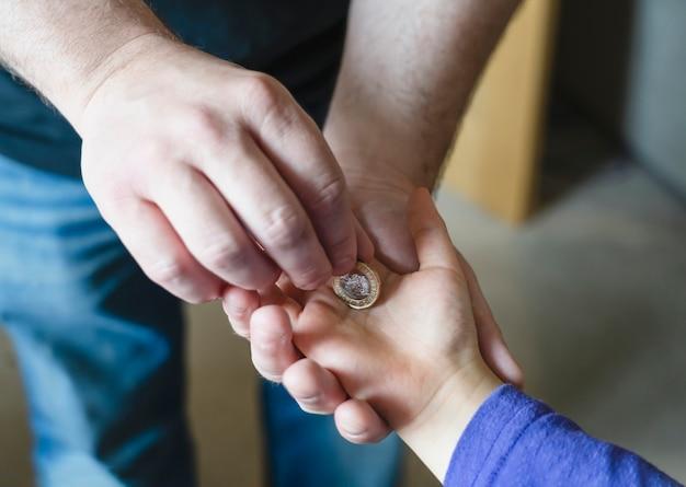 Pai dando uma moeda de uma libra para seu filho, colheita vista da mão de homem de crianças, colocando a mão de criança mony coinon. o pai dá dinheiro à criança.