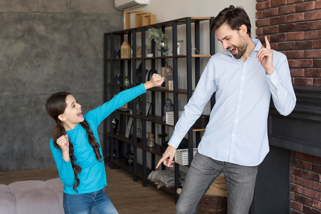 Pai de alto ângulo, ensinando a menina a dançar