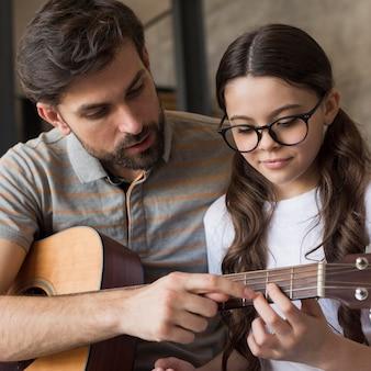 Pai de alto ângulo, ensinando a menina a tocar violão