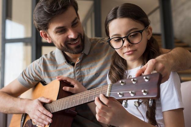 Pai de ângulo baixo, ensinando a menina a tocar violão
