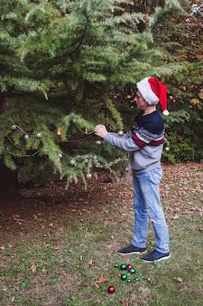 . pai de chapéu vermelho de natal a decorar a árvore de natal ao ar livre no quintal da casa antes das férias