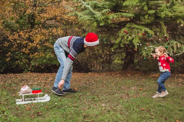 Pai de chapéu vermelho de natal preparar caixas de presentes para a filha perto de árvore de natal ao ar livre no quintal da casa.