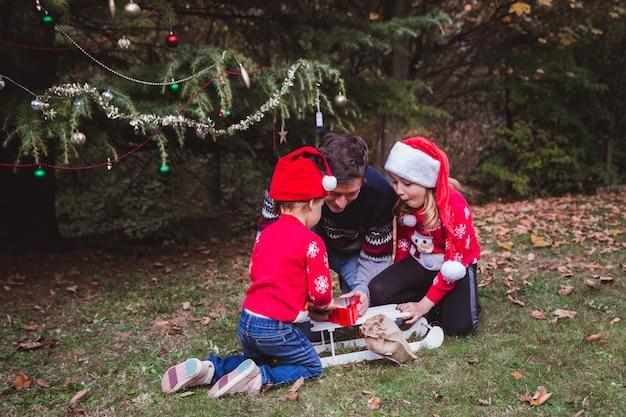 Pai de chapéu vermelho de natal preparar caixas de presentes para filhas perto de árvore de natal ao ar livre no quintal da casa.